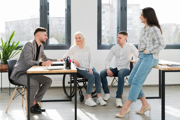 Woman in wheelchair and coworkers at office conversing