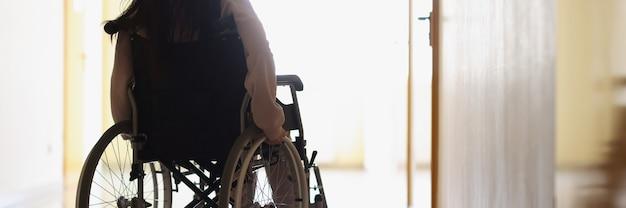 Woman in wheelchair in dark hallway looks out window