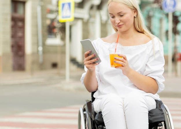 Woman in wheelchair having a drink and using smartphone with copy space