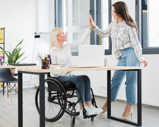 Woman in wheelchair high-fiving her female coworker at the office