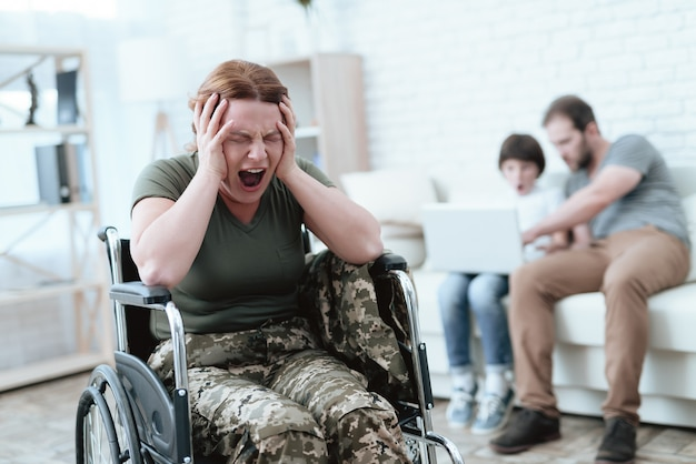 Woman in a wheelchair is in pain shes in military uniform
