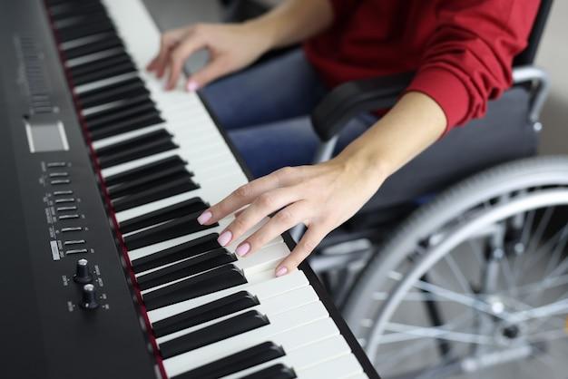 Woman in wheelchair is pressing piano keys