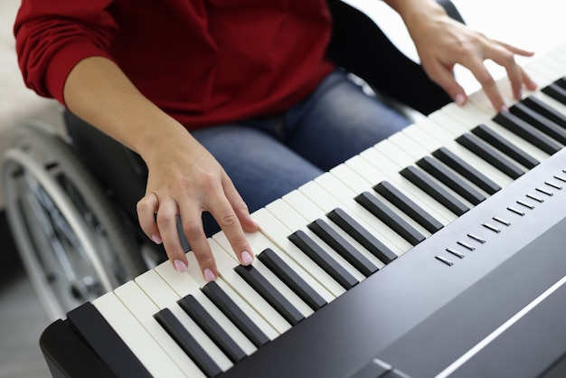 Woman in wheelchair is studying piano closeup