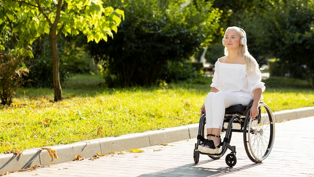 Woman in wheelchair listening to music outdoors