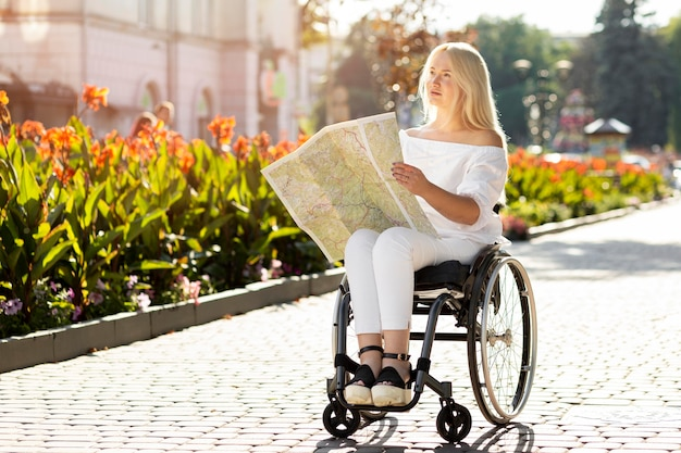 Woman in wheelchair looking at map outdoors