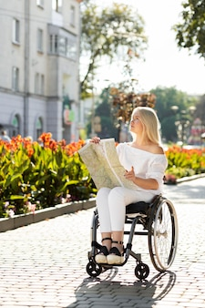 Woman in wheelchair looking at map outside