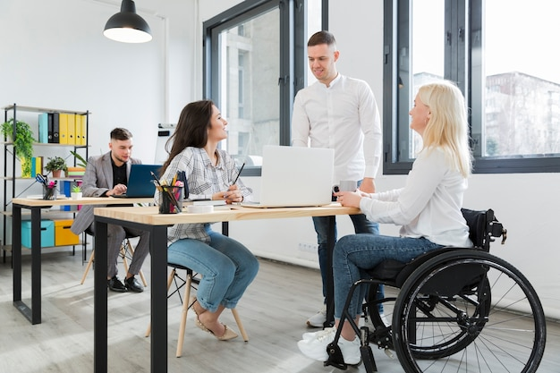 Woman in wheelchair at the office along with coworkers