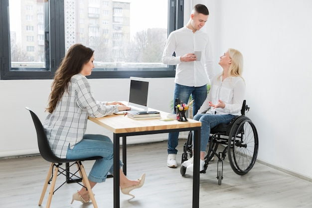 Woman in wheelchair at the office with coworkers
