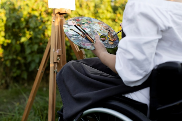 Woman in wheelchair outdoors in nature painting on canvas and canvas