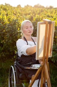 Woman in wheelchair outdoors in nature painting on canvas