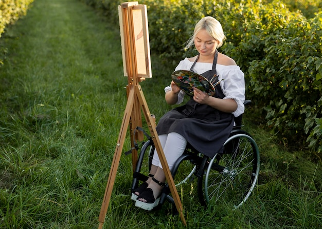 Woman in wheelchair outdoors in nature painting with easel