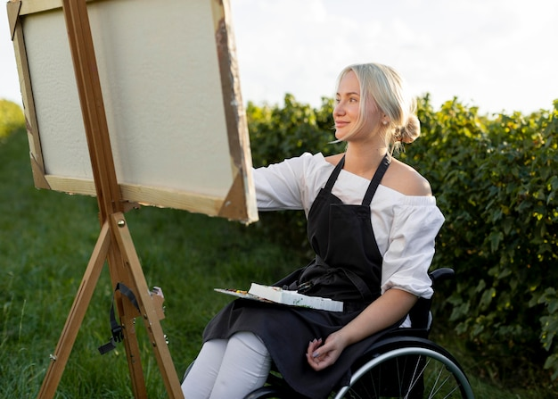 Woman in wheelchair painting in nature on canvas