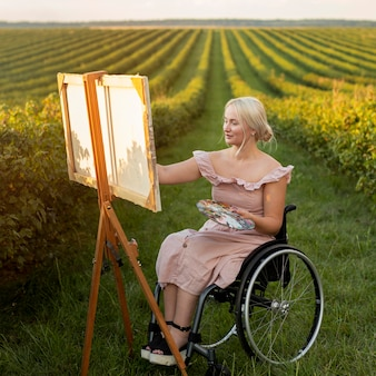 Woman in wheelchair painting outdoors