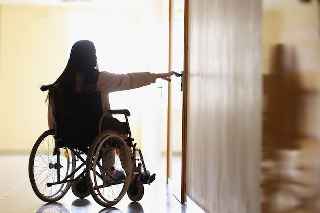 Woman in wheelchair reaches out to open handle of door in dark hallway