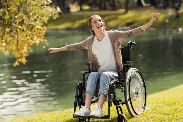 A woman in a wheelchair sits on the shore of a lake.