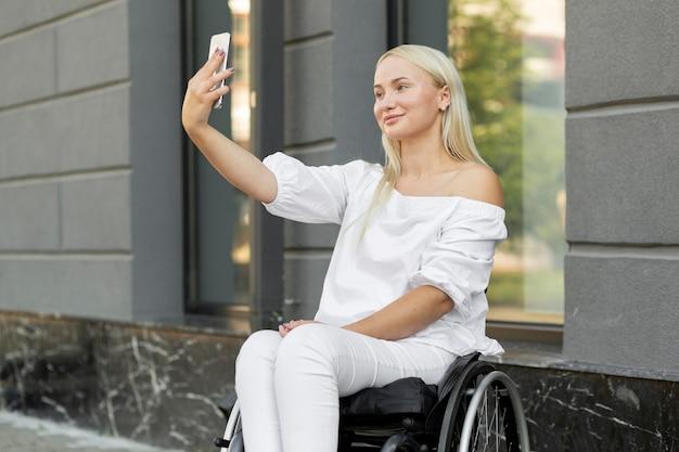 Donna in sedia a rotelle prendendo selfie con lo smartphone