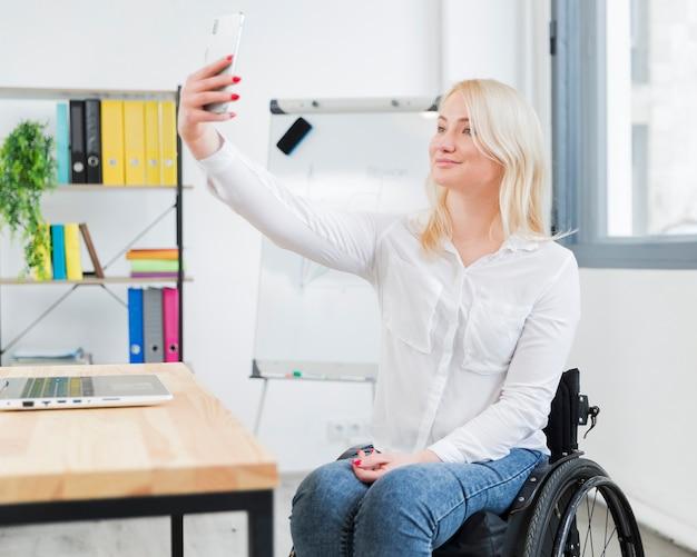 Woman in wheelchair taking selfie at work
