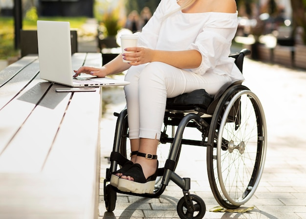 Woman in wheelchair using laptop outdoors while having a drink