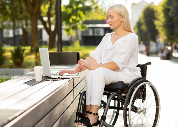Woman in wheelchair using laptop outdoors