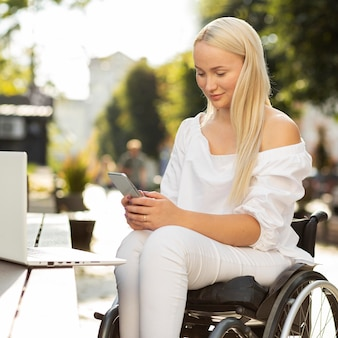 Woman in wheelchair using smartphone outdoors with laptop