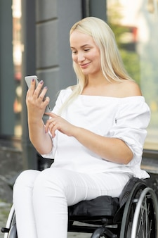 Woman in wheelchair using smartphone