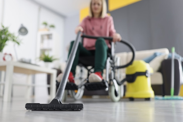Woman in wheelchair vacuuming floor at home closeup. life of disabled people concept