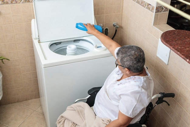 Woman in wheelchair washing clothes in washing machine