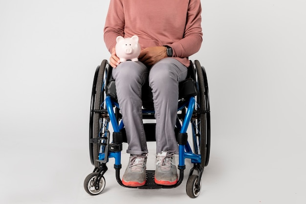 Woman in a wheelchair with a piggy bank