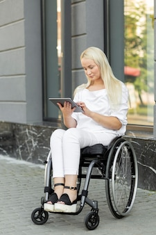 Donna in sedia a rotelle con tablet