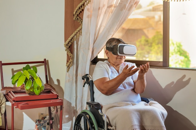 Woman in wheelchair with virtual reality glasses