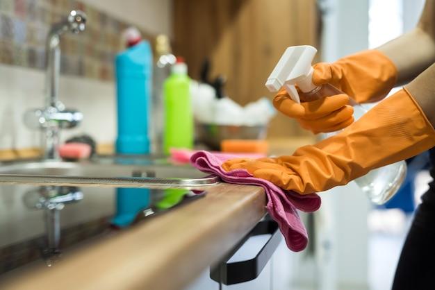 ゴム手袋をはめたスポンジで台所の机の表面を掃除している女性。家事