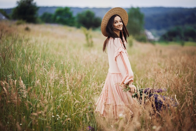 Woman whirls with bouquet of lavander on green field