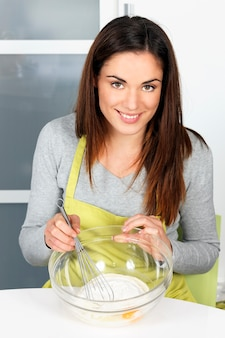 Женщина взбивает тесто на кухне