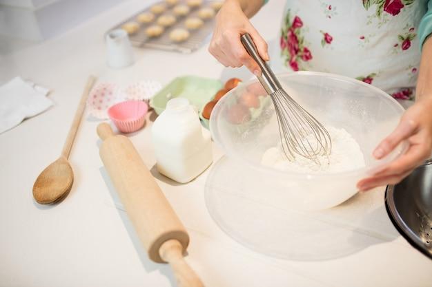 Woman whisking flour in bowl