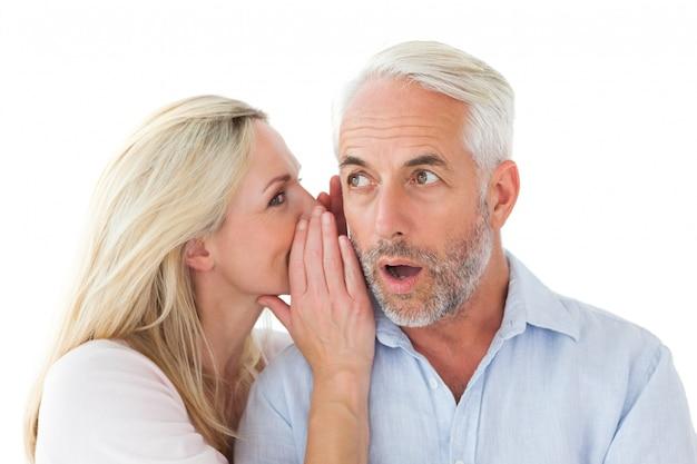 Woman whispering a secret to husband