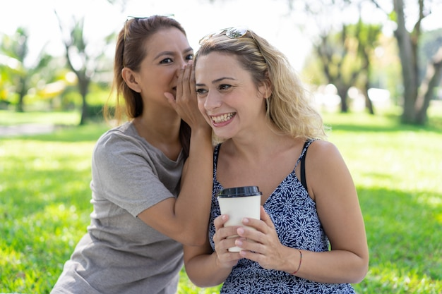 Woman whispering secret to smiling girlfriend in park