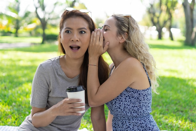 Woman whispering secret to surprised female friend in park