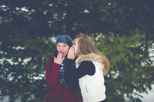 Donna che bisbiglia sull'orecchio della donna mentre le mani sulle labbra