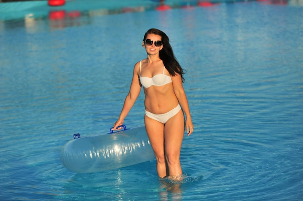 A woman in a white bathing suit with an inflatable circle in a water park
