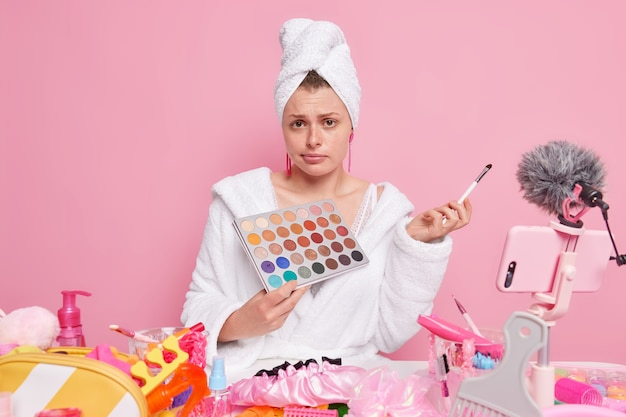 Woman in white bathrobe and towel holds eyeshadow palette and cosmetic brush broadcasting about makeup to subscribers isolated on pink.