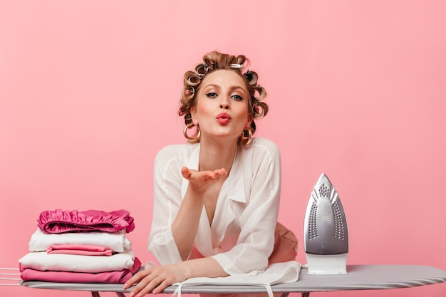 Woman in white blouse blows kiss and poses with iron