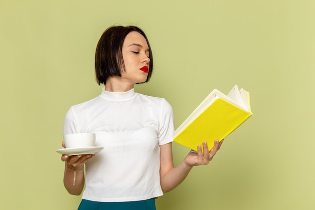 Woman in white blouse and green skirt holding cup of tea and reading a book