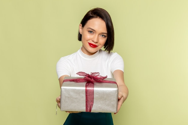 Woman in white blouse and green skirt holding present box