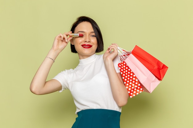 Woman in white blouse and green skirt holding shopping packages and lipstick