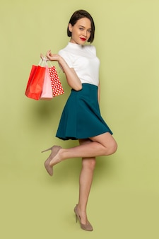 Woman in white blouse and green skirt holding shopping packages