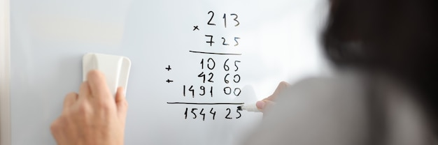 Woman on white board adds math numbers