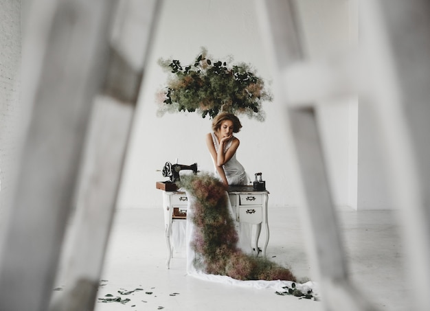Woman in white clothes sits in a room with flowers and sewing machine