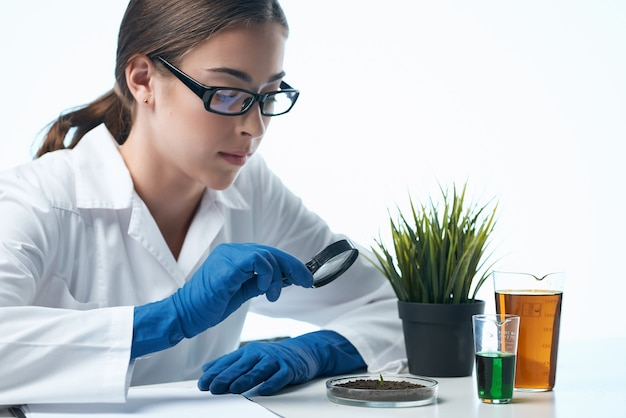 Woman in white coat examines plants microbiology