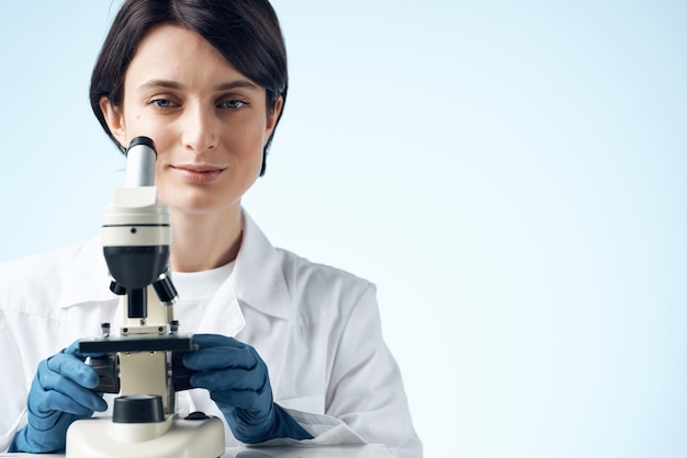 Woman in white coat laboratory science microscope analyzes