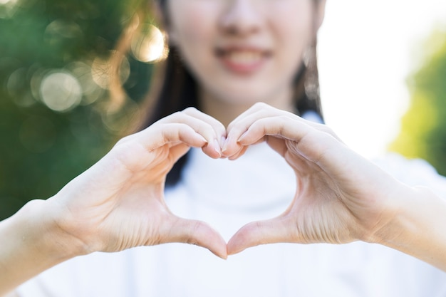 A woman in a white coat making a heart shape with both hands
